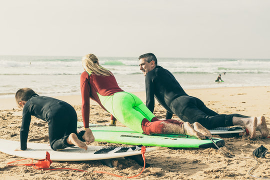 Family lying on surfboards on beach. Parents and little son in wetsuits lying on boards and learning surfing on sandy sea coast. Water sport concept