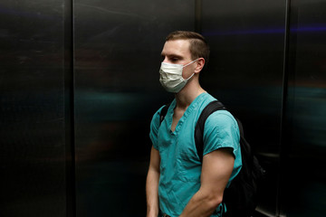 Dennis D'Urso, a resident ER doctor at Holy Cross Hospital, rides in an elevator as he leaves his apartament to go to work, in Miami