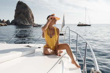 Relaxed woman in sun hat enjoying ocean voyage, sailing on the luxury yacht near the beautiful rocky coast during a sunset. Concept of a summer rest on the sea.Young happy woman enjoys sunset from the