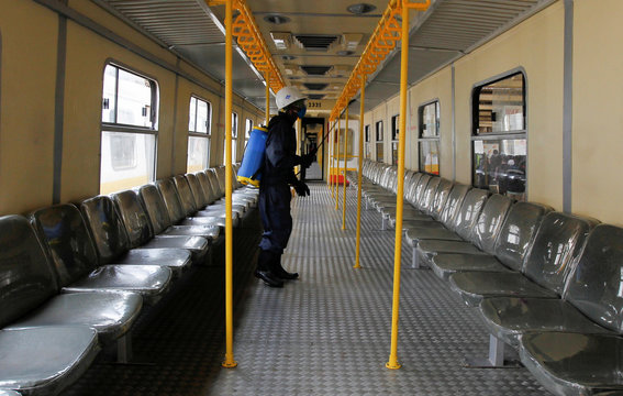 An employee of the Kenya Railways Cooperation sprays disinfectant inside a passenger train carriage before a curfew, as a measure to contain the spread of the coronavirus disease (COVID-19), in Nairobi