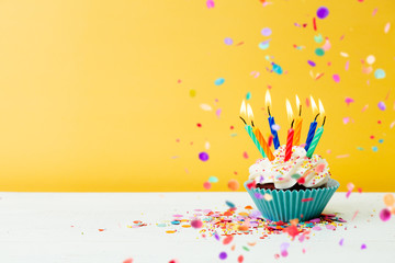 Birthday cupcake with many candles and confetti on yellow background