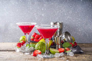 Summer cold alcohol drink. Strawberry margarita cocktail, with lime, mint and fresh strawberry on rustic wooden background