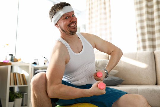 Quarantined man holding dumbbells in his hands