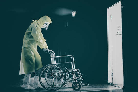 Doctor in a protective suit with wheelchair, covid-19 pandemic, horror.