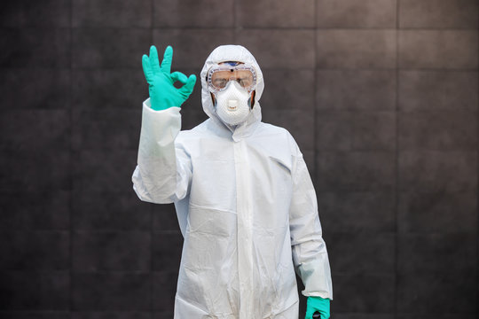Portrait of man in sterile uniform and mask standing outdoors and showing okay sign. Surfaces are all sterilized from corona virus/ covid-19.