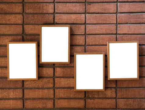 Four white blank picture frames hanging on the red brick wall background.