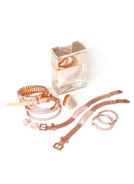 Rose gold jewelry and perfume bottle