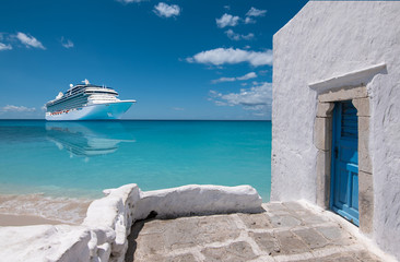Wall Mural - Cruise ship in Mykonos, Greece, Europe. Luxury Greek travel vacation with whitewashed architecture and blue door. Luxury white cruise vessel on the sea.
