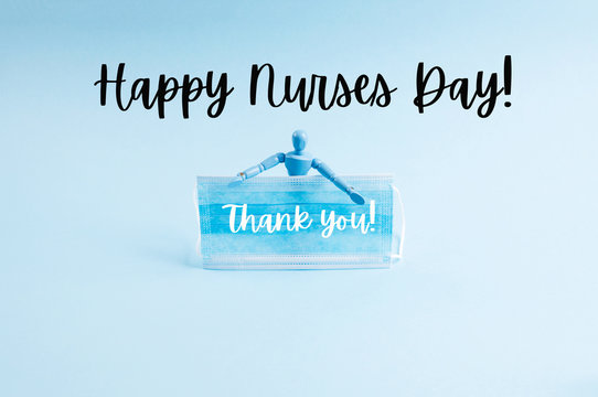 Covid-19 coronavirus pandemic concept with wooden marionette holding medical face mask with text Happy nurses day on blue. Thank you.