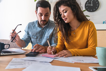 Stressed man and woman talking about family budget,  calculating household bills and expenses at desk stock photo