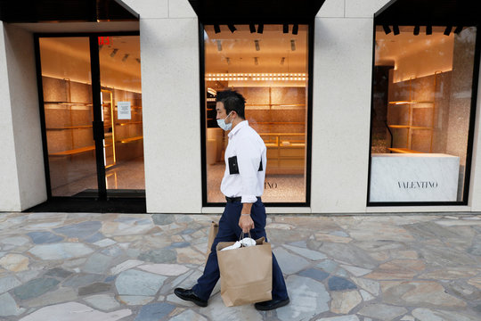 A man walks past an empty luxury shop in the tourist district of Waikiki as many businesses have temporarily closed across Hawaii due to the business downturn caused by the coronavirus disease (COVID-19) in Honolulu