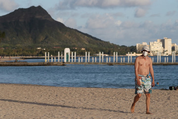 A beachgoer wearing a protective mask walks down Waikiki Beach, with Diamond Head mountain in the background, during the spread of the coronavirus disease (COVID-19) in Honolulu