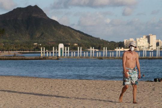 A beachgoer wearing a protective mask walks down Waikiki Beach, with Diamond Head mountain in the background, during the spread of the coronavirus disease (COVID-19) in Honolulu