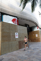 A runner goes past a boarded up shopping center in the tourist district of Waikiki as many businesses are temporarily closed across Hawaii due to the business downturn caused by the coronavirus disease (COVID-19) in Honolulu