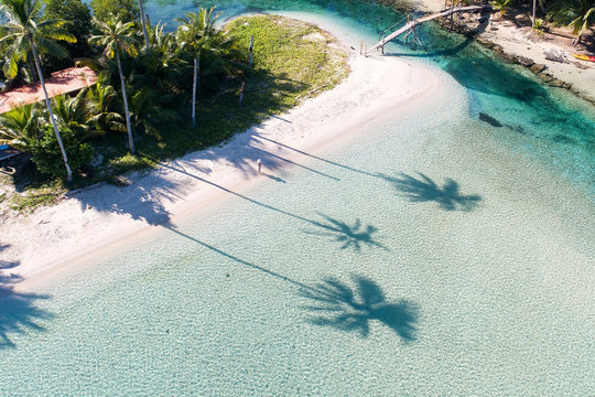 View of palm tree shadow silhouettes on tropical beach next to wooden foot bridge at Bang Bao Bay on Koh Kood island, Thailand