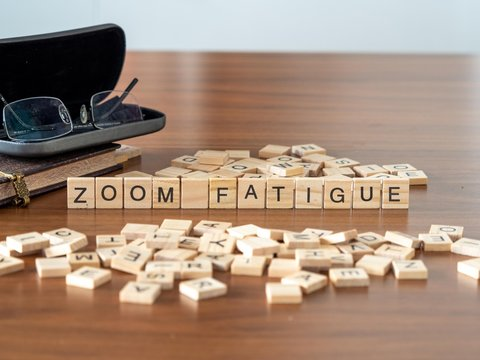 zoom fatigue concept represented by wooden letter tiles on a wooden table with glasses and a book