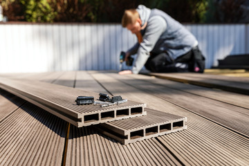 wpc terrace construction - worker installing wood plastic composite decking boards Wall mural