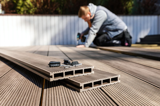 wpc terrace construction - worker installing wood plastic composite decking boards