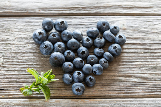 heart of fresh blueberries on wooden background