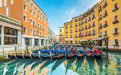 Venice horizontal pictorial cityscape, Italy, Europe.Gondola Bacino Orseolo station with gondolas at their moorings on background of Small Ponte Tron at rio Orseolo canal.