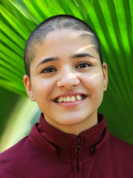 Close-up Portrait Of Smiling Woman With Shaved Head Against Plants