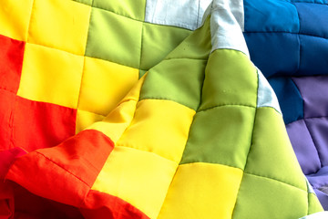 Rainbow patchwork quilt fragment. Colorful handmade ethnic blanket. Worn clothes reuse concept.