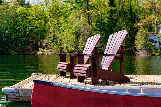 Two Adirondack chairs on a wooden dock facing the waters of a lake in Ontario, Canada. A red canoe is tied to the pier.