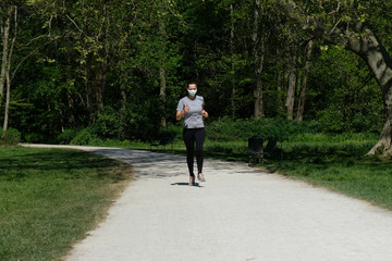 Woman running during coronavirus pandemic with mask in park