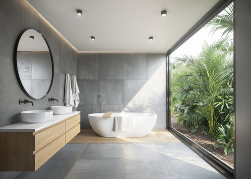Grey concrete tiled bathroom with opening to a jungle garden a round mirror and a bathtub