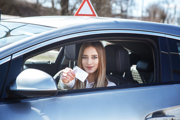 Joyful girl driving a training car with a drivers license card in her hands Fototapete