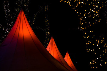 Close-up Of Illuminated Tents Against Christmas Lights At Night