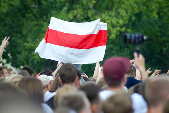 White-red-white flag at a mass event over heads against a background of green foliage of trees. White-red-white flag historical and cultural treasure of Belarus (1918, 1991–1995).
