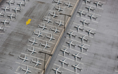 Lockdown of flights concept: Composite image of a parking lot shot from above and 3d rendered airplanes temporarily retired due to very reduced number of flights.