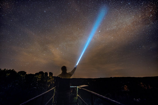 Digital Composite Image Of Man Holding Flashlight Against Star Field