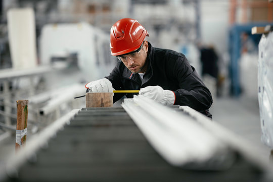 Portrait of worker in factory. Young handsome man working in factory.
