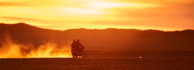 Foto op Canvas Rood traf. On a motorcycle in the Gobi desert. Dust from under the wheels. Wild Mongolian road.