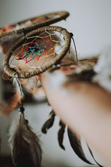 Cropped Hand Touching Dreamcatcher In Home