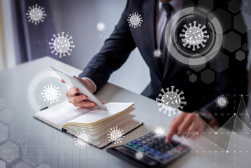 Accountant planning budget during pandemia. Virtual virology graphics. Closeup of business leader using calculator, tablet and notebook at workplace. Accounting concept