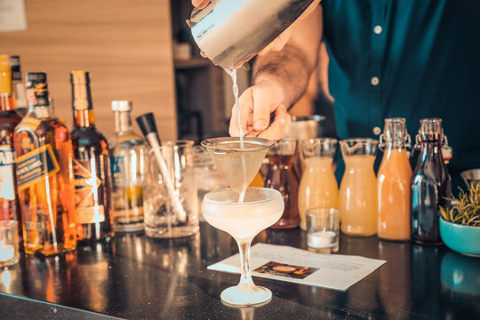 The expert bartender is making a cocktail at the bar. Man preparing cocktails.