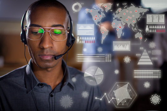 Focused African American man with headset looking down. Front view of call center operator with virtual global coronavirus spread infographics. Call center concept