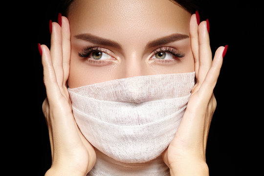 Beautiful woman with bandage face mask. Fashion eye make-up. Beauty surgery or protection hygiene in covid-19 pandemic
