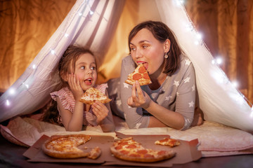 Papiers peints Pizzeria Family bedtime. Mom and daughter eat pizza in a tent. Pretty young mother and lovely girl having fun in children room.