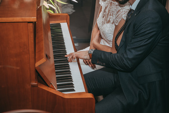 Midsection Of Couple Playing Piano