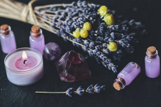 Herbal magick in wicca and witchcraft using lavender infused water. Purple lit burning candle, amethyst pyramid crystal, dried lavender flowers on a black table altar with pastel colored small potions