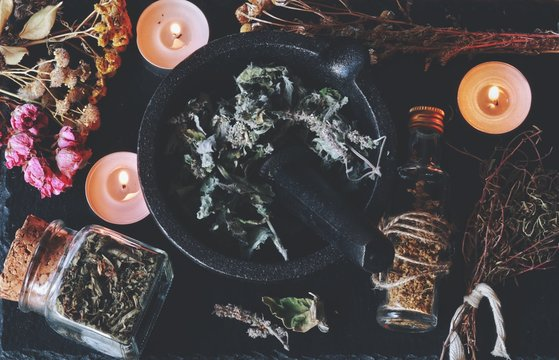 Kitchen witchery using herbs and spices found at home. Herbal magick in wicca and witchcraft with mortar and pestle in the center filled with dried melissa herb. Burning white candles, jars, bottles