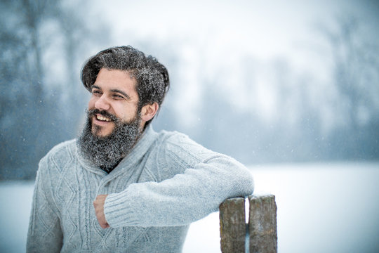 Happy Young Bearded Man With Arms Crossed Standing During Snowfall