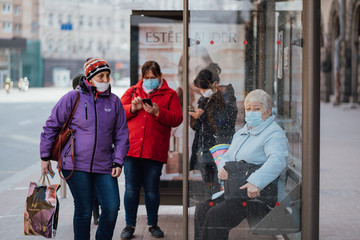 Kiev, Ukraine, 28 March 2020, people at the street in protective facial masks wainting bus at bus stop