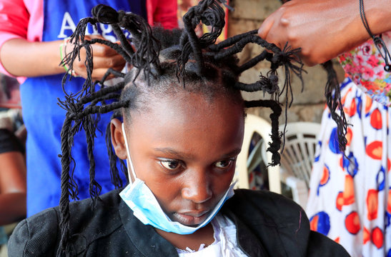"""Martha Apisa gets plaited with the """"coronavirus"""" hairstyle, designed to emulate the prickly appearance of the virus under a microscope as a fashion statement against the spread of the coronavirus disease (COVID-19) in Kibera, Nairobi"""