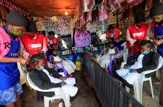 """Martha Apisa and Stacy Ayuma get plaited with the """"coronavirus"""" hairstyle, designed to emulate the prickly appearance of the virus under a microscope as a fashion statement against the spread of the coronavirus disease (COVID-19) in Kibera, Nairobi"""