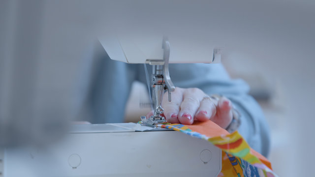 Female sewing together face mask with a sewing machine